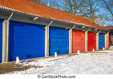 Garage Doors in in blue and red next to each other on a Snowy Winter Day