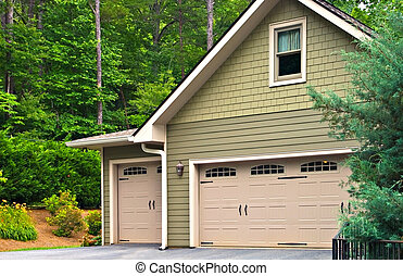 Garage doors on a modern house. Double doors with windows on one side and an off-set single beside it.