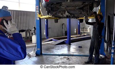 garage owner talking with customer on phone and mechanic repairing car.