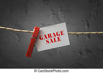 Garage sale card attached to a rope with clothes pins