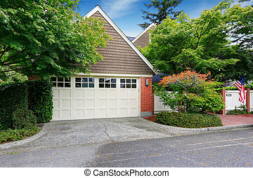 Garage with clapboard siding and brick trim