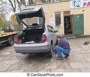 Garage worker in uniform changes machine wheels.