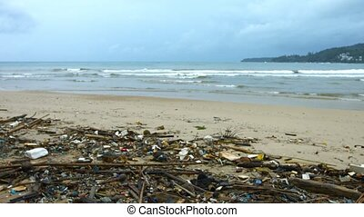 Sandy tropical beach in Southeast Asia, almost completely covered in litter and garbage, as gentle, tropical waves break on an overcast day. Video UltraHD