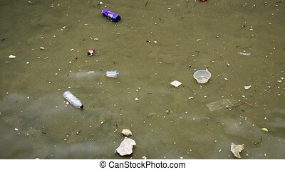 Plastics and other rubbish float in the shallow sea water beneath a poor fishing village in southern Thailand. Ultra HD stock footage
