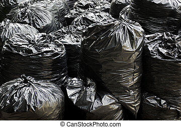 A pile of black garbage plastic bags with tons of trash