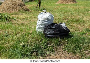 garbage bags in green meadow