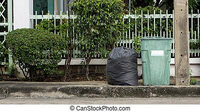 garbage bin in the park beside the walkway
