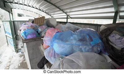 Garbage bins filled with plastic trash bags.