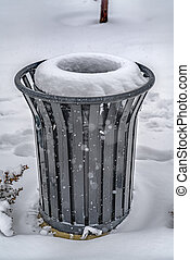 Garbage can on snow covered ground in winter
