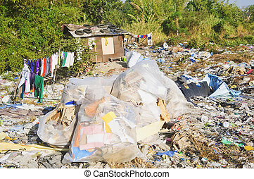 Shanty and sacks of refuse in a garbage dump