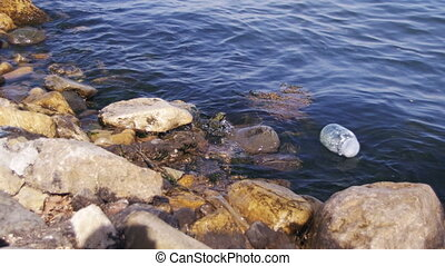 Garbage Floats in the Caspian Sea near the Stones on the Embankment