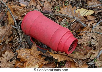 garbage from a dirty old red plastic bottle of a thermos lies in brown dry fallen leaves