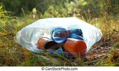 Garbage in a plastic bag plastic bottles lie on the grass,...