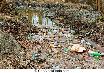 garbage in the forest on the river, pollution of reservoirs