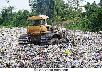 Garbage Landfill - Bulldozer spreads garbage in a landfill; ...
