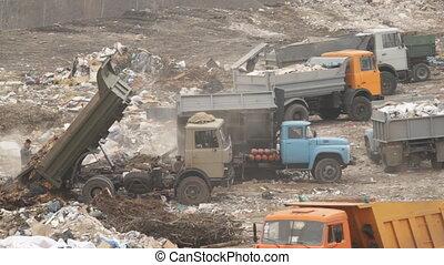 Garbage machines unload garbage on a municipal dump in...