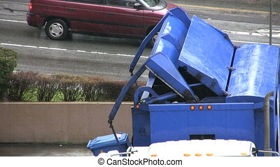 Garbage Recycling Truck - A recycling garbage truck dumps a...