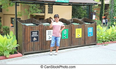 Garbage separation. Child throwing apple into the trash -...