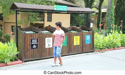 Garbage separation. - Kid giving paper cup in recycle bin....