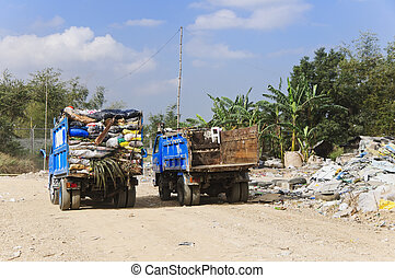 One garbage truck overflowing with trash in old sacks; other truck is empty