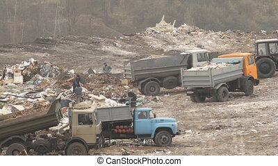 Garbage trucks unload garbage on a dump