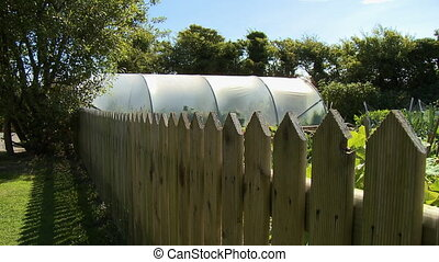 Garden and Greenhouse Behind Wooden Fence - Steady, medium...