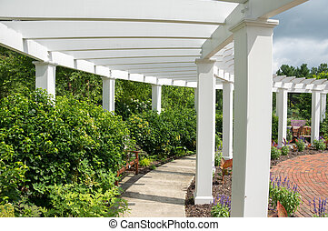 Garden Arbor - An arbor in a garden surrounded by bushes and...