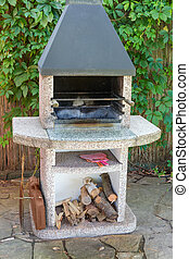 Garden barbecue fireplace outdoors against reed stems fence, maiden grapes