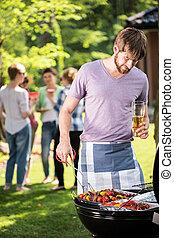 Garden barbecue with friends - Man preparing food on garden ...