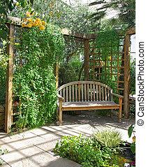 A solitary wooden bench against trellicework in a green garden.