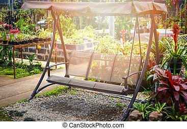 garden bench outdoors / modern swing bench with the roof in the garden flowers