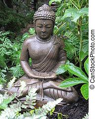 Dark Buddha seated in leafy shaded garden