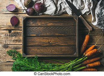 Garden carrots and beetroots with wooden tray in center