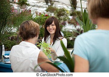 Customers in a garden center standing in line at cashier