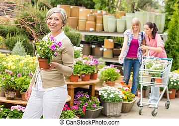 Garden center senior lady hold potted flower - Senior lady...