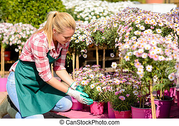 Garden center woman kneeling by potted flowers - Garden...