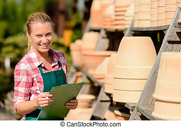 Garden center woman worker standing by clay pots shelf smiling