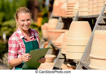 Garden center woman standing by clay pots - Garden center...