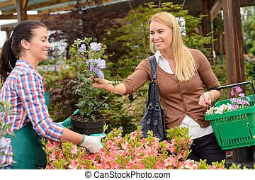 Garden center worker selling potted flower customer - Garden...