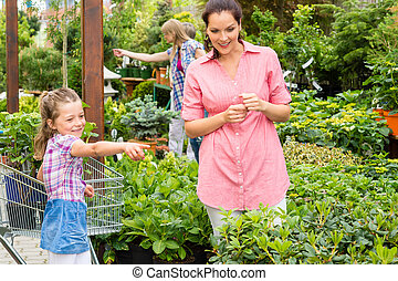 Garden centre child mother at plant market