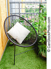 Garden chair with pillow on balcony at home in appartment on lawn grass with house plants flowers. Garden veranda modern terrace. Home gardening, houseplants. Rest relaxation place green oasis in city