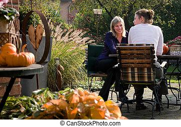 garden conversation - two girlfriends talking while sitting...
