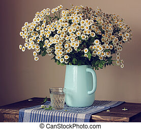 Garden daisies in a jug on the table. Still life with flowers.