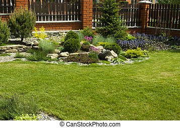 Garden design - Green lawn in a colorful landscaped formal...