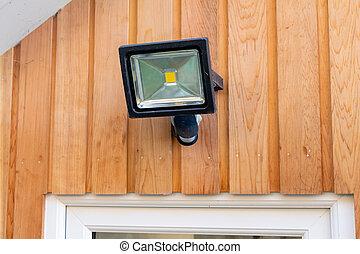 Garden flood sensor light fixed to a wooden wall above a door