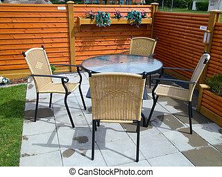 Garden furniture in a beautifull blooming patio deck