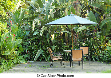 Garden furniture - rattan chairs and table under umbrella on a wooden floor by the banana trees background at garden