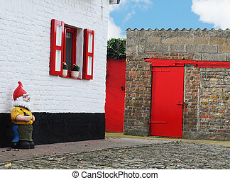 Garden gnome guarding picturesque farmhouse and barn bright with bright red painted doors