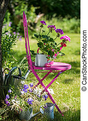 Garden idyll - Garden flowers with watering cans and chair