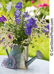 Garden idyll with flowers on a little garden table